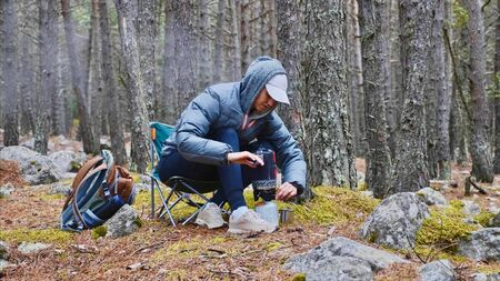 Woman in forest camping boils tea in a gas burner and pours it into a mug.