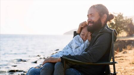 Cute child girl sits on hands of her father and they embracing together