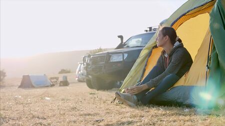 Young woman is put on a shoes near tourist tent in expedition camp and goes away