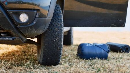 A camping equipment is on the ground next to off-road vehicle Stok Fotoğraf