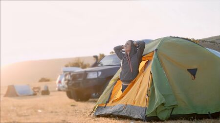 Young woman wakes up and comes out from tourist tent and stretches