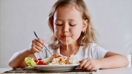 A little child girl is eating spaghetti at home Stok Fotoğraf