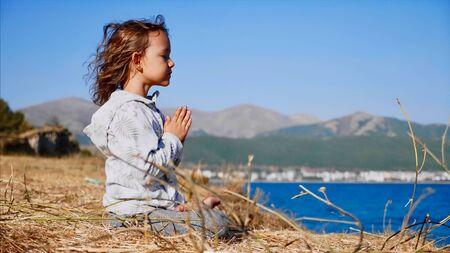 Cute little child gurl meditating alone in lotus pose at lake shore Stok Fotoğraf