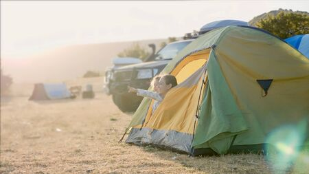 Mother with little daughter wakes up and looks out from tourist tent Stock fotó