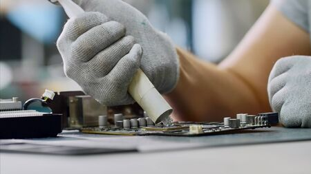 PC repair and maintenance in service center. Repairman puts thermal paste on processor of graphics chipset. Technician of computer technology at work.