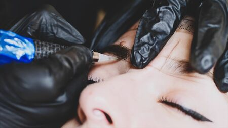 The microblading master in black gloves is filling up the shape of an eyebrow with a pigment holding with one hand womans head, close-up, camera is above the client.