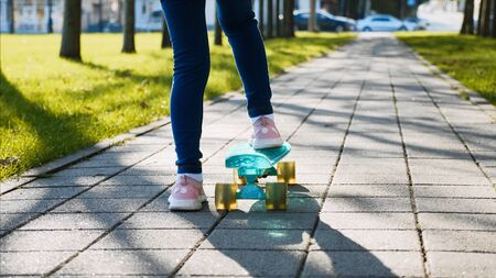 Close-up back view of legs of a child girl in jeans and pink sneakers riding a skateboard in the park along the green grass in sunny weather.