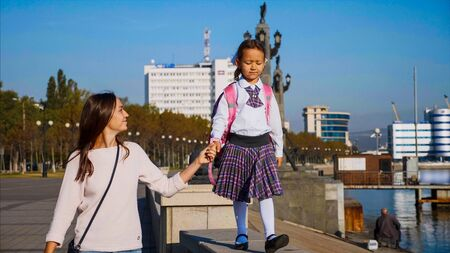 School girl is walking on railing of seafront with mom, front view.