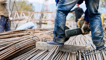 Close-up view of legs in foreground of a worker man in blue jeans, cutting rebar with a saw blade at construction site. Right leg is on the metal tubes which are on wooden stud, sparks from process.