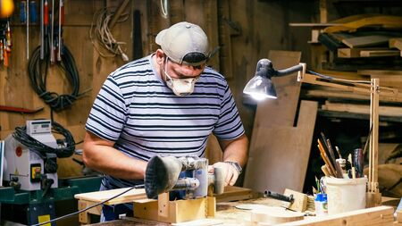 Male carpenter worker is grinds the wood detail. Craftsman polishing with grinding machine at wood workshop.