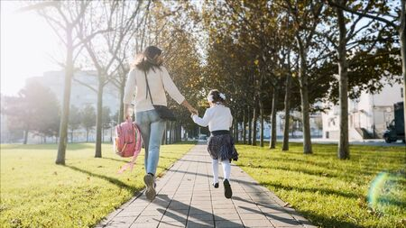 A woman and little girl in school uniform running in park, back view