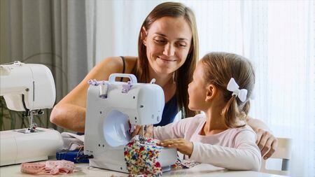 A girl is sewing on a machine. Mom shows how to work with equipment. Close-up. Stok Fotoğraf