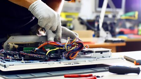 Technician works in service center. Repairman detaches power supply repairs computer monoblock in workshop. He disconnects wires, takes out and puts detail on table, continues to diagnose monitor.