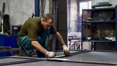 Man worker locksmith measures tape measure length of metal bars. He makes marks with pencil in workshop. He is in uniform and gloves in his workplace. Work with metal in production. Stok Fotoğraf