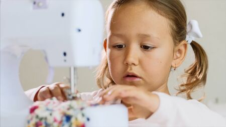 Close-up of a little girl who is making stiches on sewing machine. Portrait. Zdjęcie Seryjne