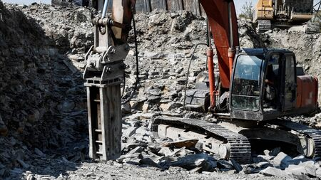 A crawl excavator hydraulic rock stone hammer is breakin rocky soil. 스톡 콘텐츠