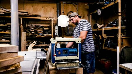 Male carpenter is working with cabinet planer machine at wood workshop Banque d'images