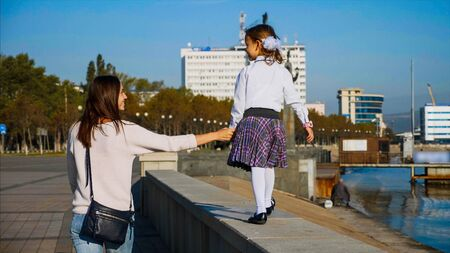 School girl is walking on railing of seafront with mom, rear view. Фото со стока