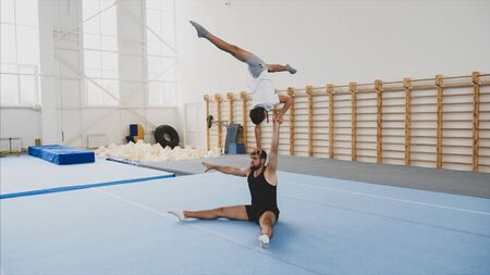 A young boy athlete is making a handstand with on hand and split on the head of a man partner, sitting in fold on the sport mat in a sport center.