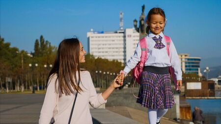 School girl is walking on railing of seafront with mom, steadicam, front view.
