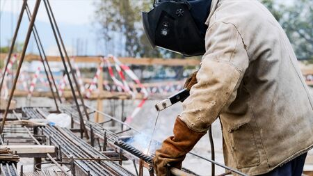 A worker at construction site is welding iron pipe with electrode in a protective uniform, orange gloves and black helmet. Sparks and smoke are allocated. Side view of an unrecognizable welder.