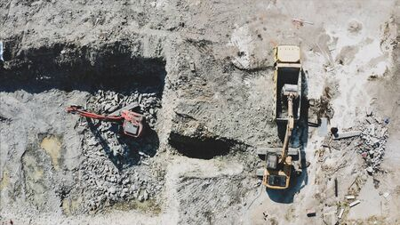 An orange crawl excavator is digging, turning and transferring the ground to the loader. Aerial top view, day time, outside.