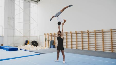 A young boy athlete is making a handstand with on hand and split on the head of a man partner in a sport center. Stok Fotoğraf