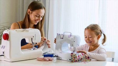 Mother and daughter is sewing on a machine together. Stok Fotoğraf