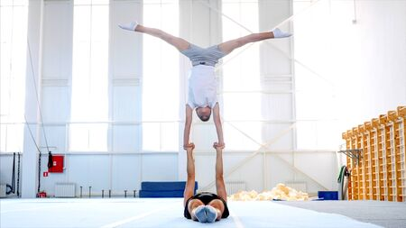 Two acrobats: a fit sporty man and a boy teenager are practicing acrobatic handstand in the big light gym. Young gymnast doing handstand on the hands of his lying male partner in sport center. Stok Fotoğraf