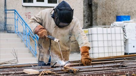 A worker at construction site is welding iron pipe with electrode in a protective uniform, orange gloves and black helmet. Sparks and smoke are allocated. Stok Fotoğraf