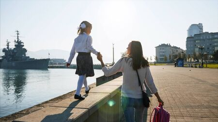 A girl in school uniform is walking on the railing of the promenade with mother. Фото со стока