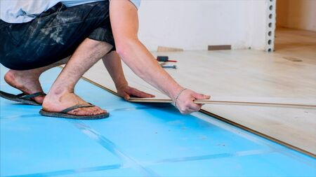 A worker is putting laminate panels together in room, the process of flooring.