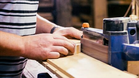 Craftsman working with grinding machine at wood workshop, hands closeup.