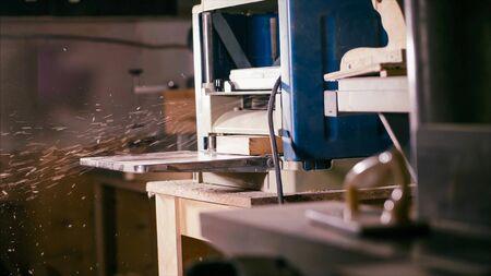 Cabinet planer machine is working with sawdust at wood workshop . Process of work surf gage machine