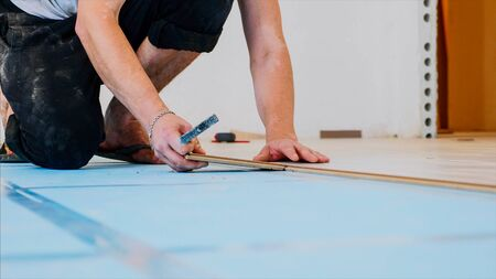 A woker is fitting laminate with piece of panel and a small hammer in the room.