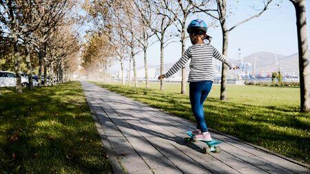 Little girl is slowly skateboarding in protective helmet.