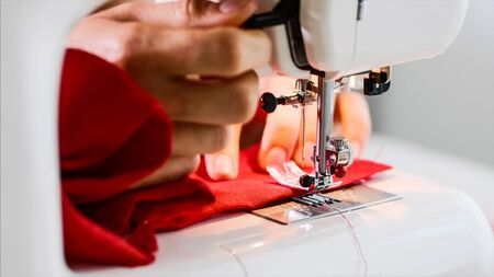 Hands of woman tailor sewing red clothing on sewing machine with straight seam.