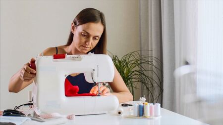 Self-employed seamstress woman working and sewing cloth on sewing machine.