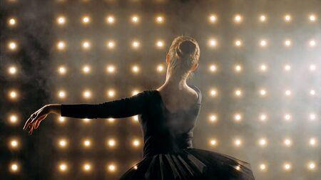 Silhouette of ballerina in black tutu is dancing ballet in the dark studio.