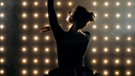 Silhouette of ballerina in black tutu is dancing ballet in the dark studio with smoke and the lights on the background. Imagens