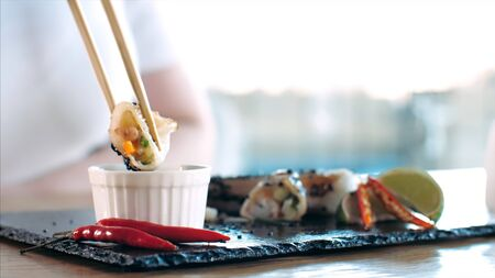 Woman takes a slice of spring roll via chopsticks, dips it in sauce and eats, close-up. 写真素材
