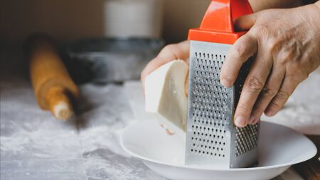 Close-up hands of mature woman is rubs a white soft cheese on a steel grater for preparing bakery at home kitchen