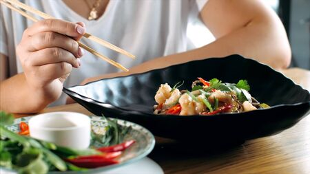 Woman eating traditional asian soba stir-fry noodles with shrimp at restaurant, close-up. Asian food concept.