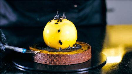 Close-up of chef is finishing make dessert with passion fruit at commercial bakery. Baker is decorating a cake Banque d'images