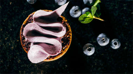 Pastry biscuit with purple cream on the table near the blueberries, close-up.