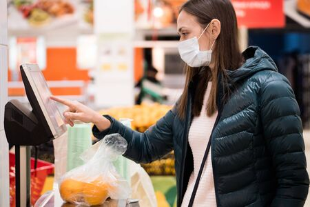 Young woman in medical masks a weighing an oranges on a scales at supermarket. Virus epidemic concept. Reklamní fotografie