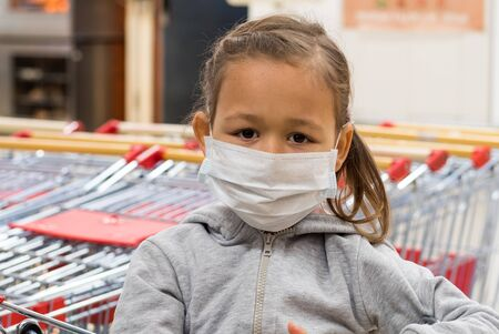 Portrait of little child girl in medical mask is gazing at camera in supermarket