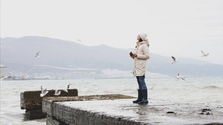 Young woman is feeding a seagulls. Seashore in storm windy weather Banque d'images - 144165589