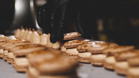Chef is assembling caramel macarons, close-up. 免版税图像