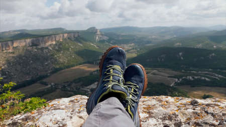 Close-up feet of resting hiker with mountains on the background 免版税图像